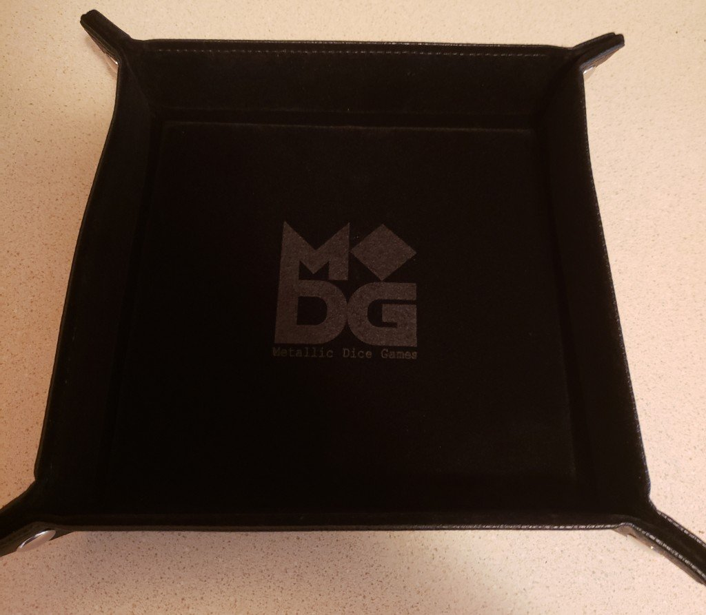 A collapsible black dice tray with a velvet inside and leather outside