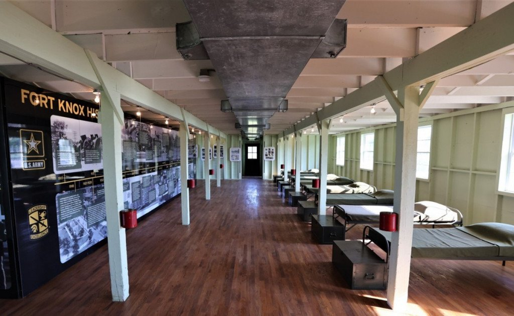 a WW2 barracks with a row of cots and a trunk for personal storage